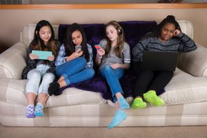 Group of young girls disengaged and distracted on mobile device